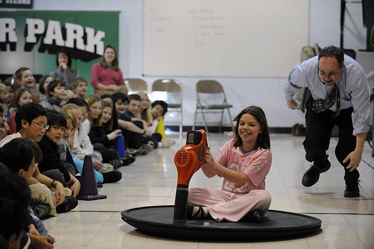 A student rides a real, working hovercraft at a science school assembly.