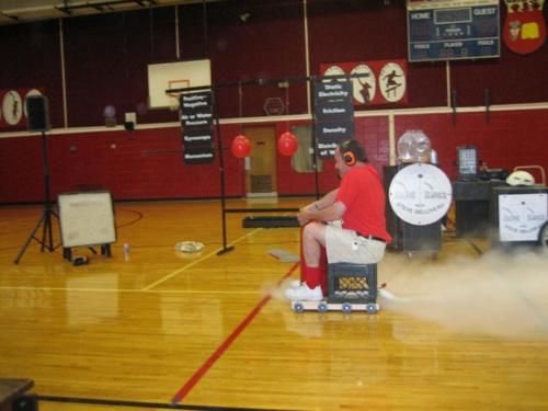 Steve rides the Rocket Car at a Science School Assembly